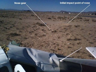 In the center of the screen, one can see the nose gear. To the right and on the near edge of the dirt road is the mark left by the initial impact of the nose.